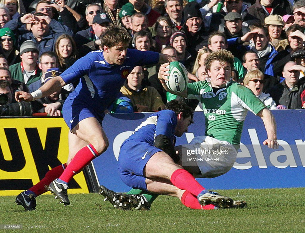 Ireland's captain Brian O'Driscoll (R) is tackled by French centre Benoit Baby (C) and French winger Cedric Heymans during their VI Nations rugby union match, 12 March 2005 at Landsdowne Road stadium in Dublin. France won 26-19.