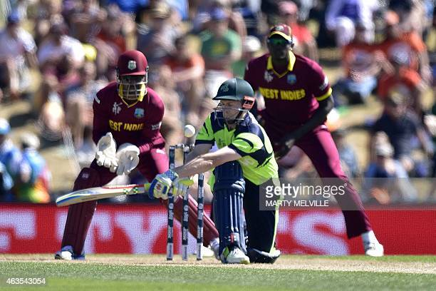 Ireland's captain William Porterfield plays a shot watched by West Indies' wicketkeeper Denesh Ramdin and captain Jason Holder during the Pool B 2015...