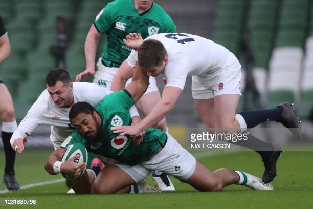 Ireland's centre Bundee Aki is tackled by England's wing Jonny May and England's centre Owen Farrell during the Six Nations international rugby union...