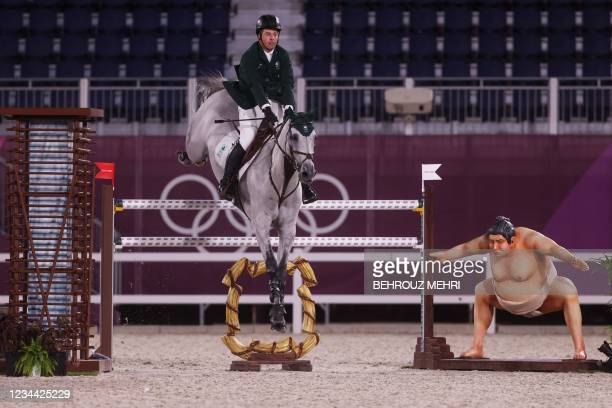 Ireland's Cian O'Connor rides Kilkenny past a small sumo wrestler statue in the equestrian's jumping individual qualifying during the Tokyo 2020...