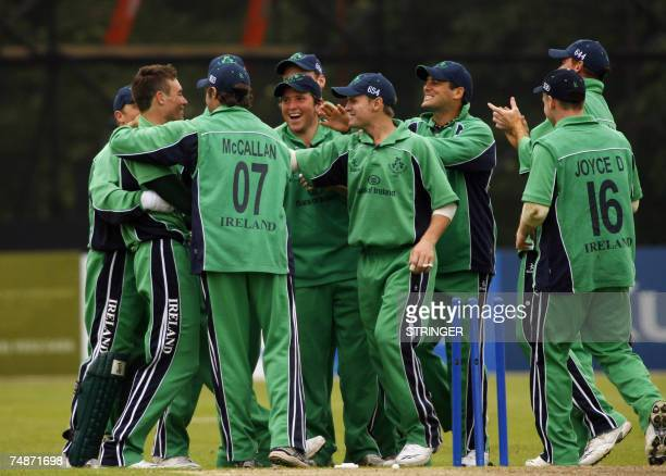 Ireland's cricket team players celebrate with Roger Whelan as he bowled out India's batsman Sachin Tendulkar 23 June 2007 during the One Day...