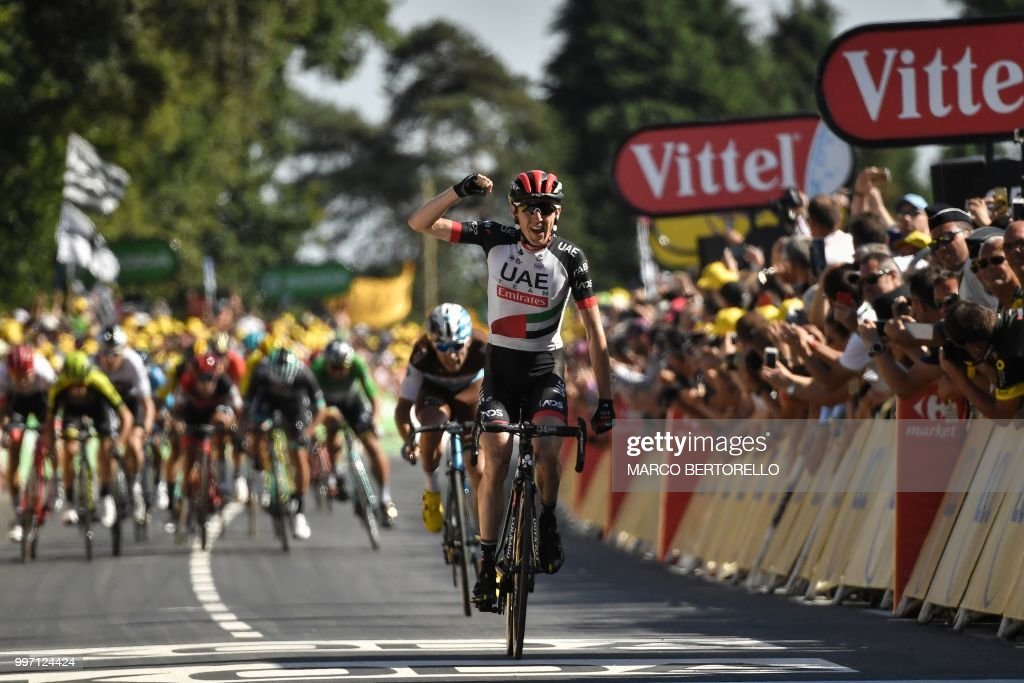 TOPSHOT - Ireland's Daniel Martin celebrates as he crosses the finish line to win the sixth stage of the 105th edition of the Tour de France cycling race between Brest and Mur-de-Bretagne Guerledan, western France, on July 12, 2018.