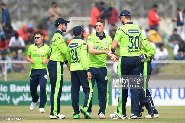 Ireland's Gareth Delany celebrates with teammates after dismissing Afghanistan's Hazratullah Zazai during the second T20 cricket match between...