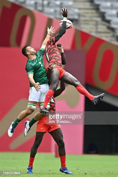 Ireland's Harry McNulty fights for the ball with Kenya's Collins Injera in the men's pool C rugby sevens match between Kenya and Ireland during the...