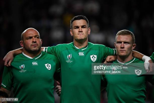 Ireland's hooker Rory Best flyhalf Jonathan Sexton and wing Keith Earls sing the national anthem before the Japan 2019 Rugby World Cup Pool A match...