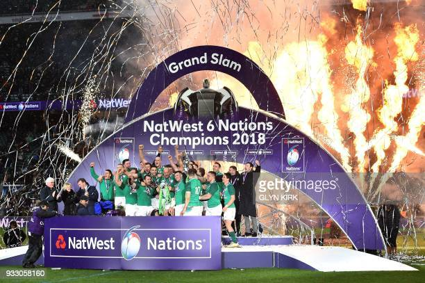 Ireland's hooker Rory Best holds the Six Nations trophy and Ireland's fly-half Jonathan Sexton the Triple Crown as Ireland players celebrate their...