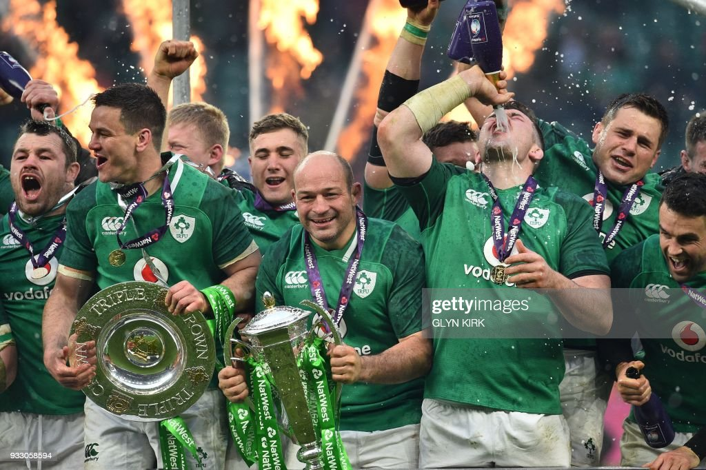 TOPSHOT - Ireland's hooker Rory Best (C) holds the Six Nations trophy and Ireland's fly-half Jonathan Sexton (2L) the Triple Crown as Ireland players celebrate their Six Nations Grand Slam victory after the Six Nations international rugby union match between England and Ireland at the Twickenham, west London, on March 17, 2018. / AFP PHOTO / Glyn KIRK
