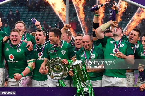 Ireland's hooker Rory Best holds the Six Nations trophy and Ireland's flyhalf Jonathan Sexton the Triple Crown as Ireland players celebrate their Six...
