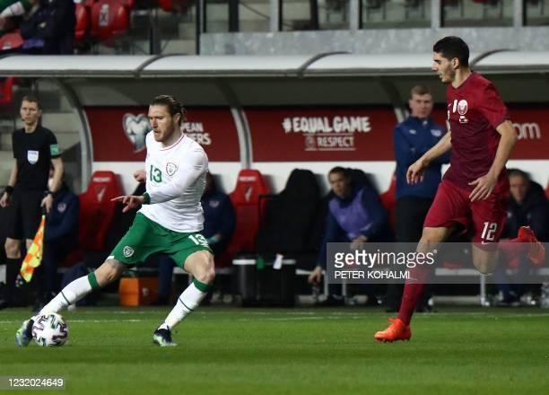 Ireland's Jeff Hendrick and Qatar's Karim Boudiaf vie for the ball during the FIFA World Cup Qatar 2022 friendly preparation football match Qatar v...