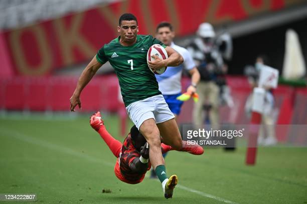 Ireland's Jordan Conroy avoids the tackle of Kenya's Jeff Oluoch in the men's pool C rugby sevens match between Kenya and Ireland during the Tokyo...