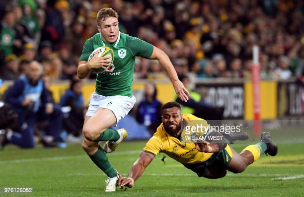 TOPSHOT Ireland's Jordan Larmour skips past the tackle of Australian Wallabies defender Marika Koroibete during the second rugby union Test match...