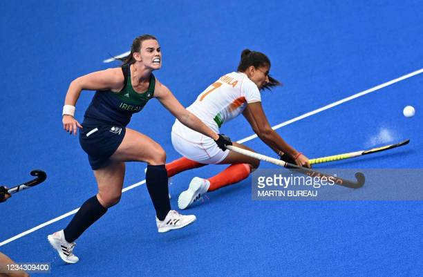 Ireland's Lizzy Holden and India's Sharmila Devi vie for the ball during their women's pool A match of the Tokyo 2020 Olympic Games field hockey...