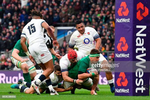Ireland's number 8 Cj Stander moves toward grounding the ball at the base of the post to score their second try during the Six Nations international...