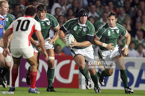 Ireland's number 8 Denis Leamy runs with ball beside teammates flanker David Wallace and lock Donnacha O'Callaghan during their rugby union World Cup...