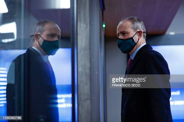 Ireland's Prime Minister Micheal Martin is reflected in glass as he leaves at the end of an EU summit at the European Council building in Brussels,...
