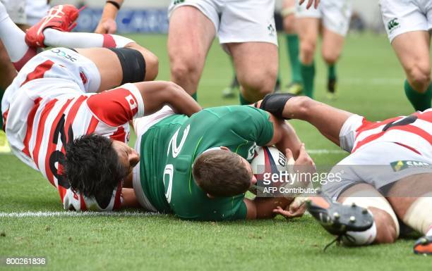 Ireland's Sean Reidy scores a try past Japan's Yoshitaka Tokunaga and Michael Leitch during their rugby union test match in Tokyo on June 24 2017 /...