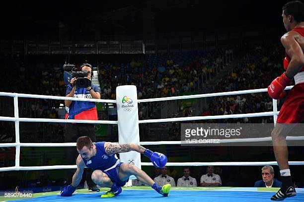 Ireland's Steven Gerard Donnelly is knocked down by Morocco's Mohammed Rabii during the Men's Welter Quarterfinal 1 at the Rio 2016 Olympic Games at...