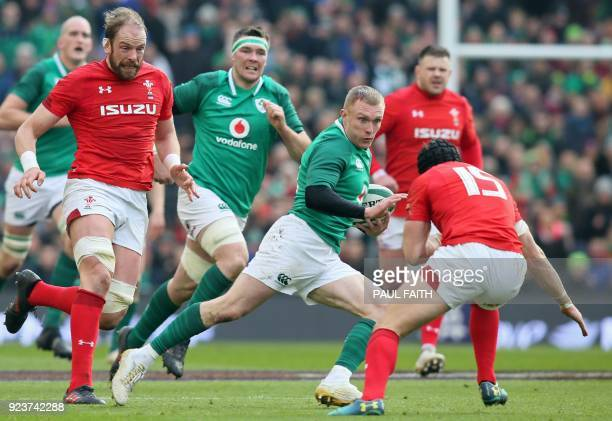 TOPSHOT Ireland's wing Keith Earls is tackled by Wales' fullback Leigh Halfpenny during the Six Nations international rugby union match between...