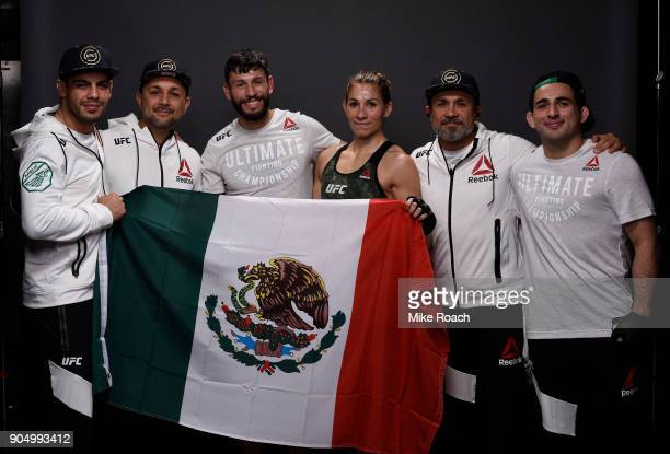 Irene Aldana of Mexico poses for a post fight portrait backstage with her team during the UFC Fight Night event inside the Scottrade Center on...