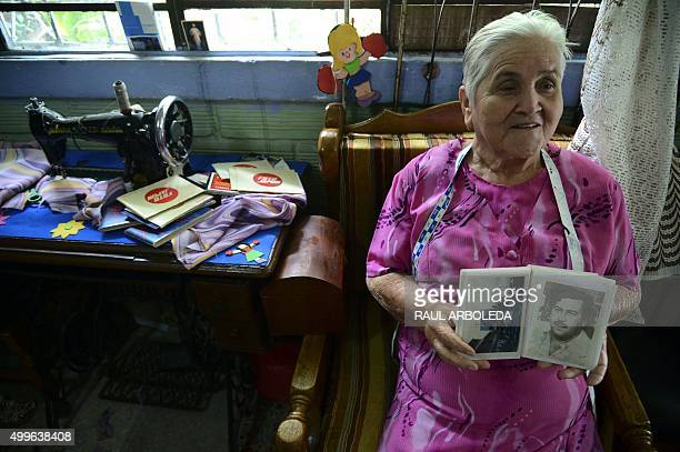 Irene Gaviria shows an album with pictures of late Colombian drug lord Pablo Escobar at her home in the Pablo Escobar neighborhood in Medellin,...