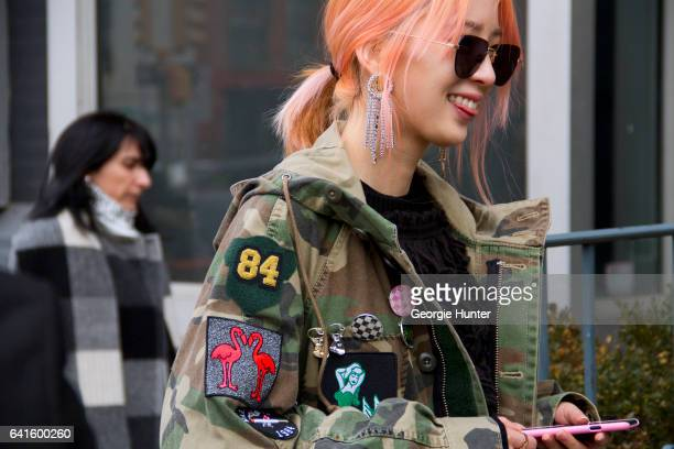 Irene Kim is seen at Spring Studios outside the Lacoste show wearing military camouflage cargo coat with badges black tasseled sweater black...