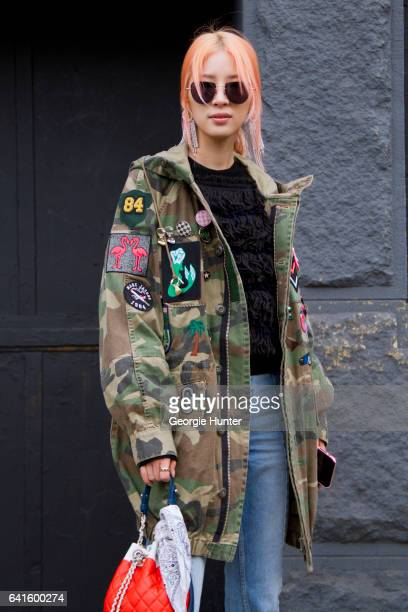 Irene Kim is seen at Spring Studios outside the Lacoste show wearing military camouflage cargo coat with badges denim jeans black tasseled sweater...