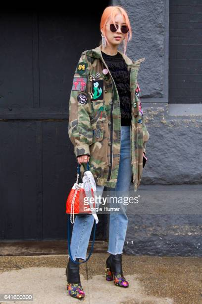 Irene Kim is seen at Spring Studios outside the Lacoste show wearing military camouflage cargo coat with badges denim jeans black ankle boots with...