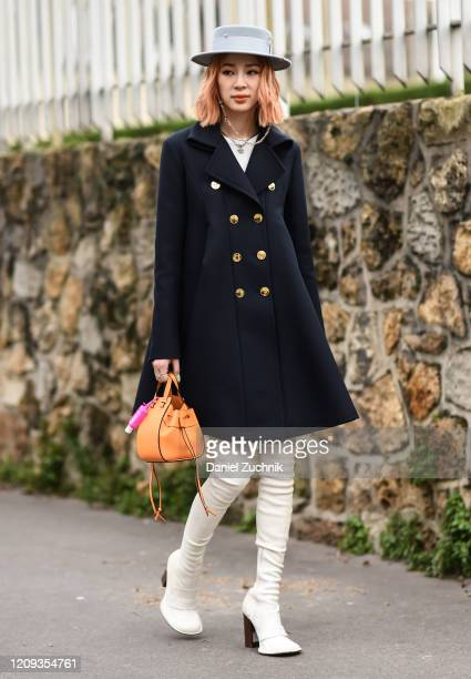 Irene Kim is seen wearing a Loewe coat, gray hat, white boots and Loewe bag outside the Loewe show during Paris Fashion Week: AW20 on February 28,...