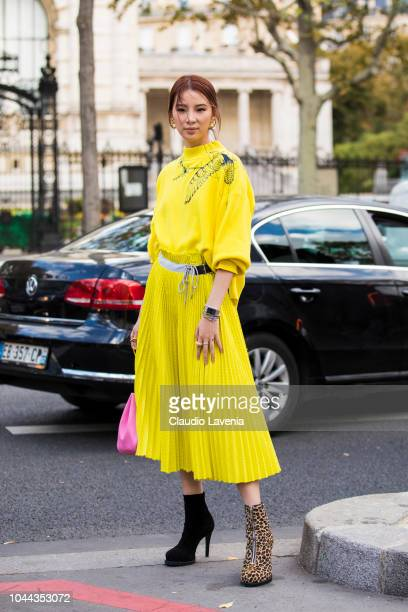 Irene Kim wearing a yellow printed jumper yellow midi skirt animal print heels and pink bag is seen after the Sacai show on October 1 2018 in Paris...