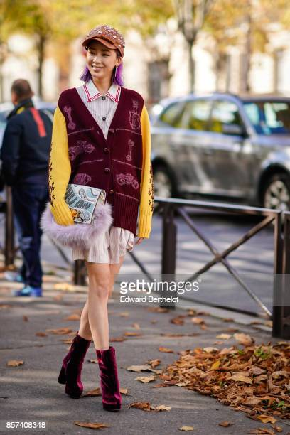 Irene Kim wears a cap hat a red jacket yellow sleeves a pleated dress red velvet shoes outside Miu Miu during Paris Fashion Week Womenswear...
