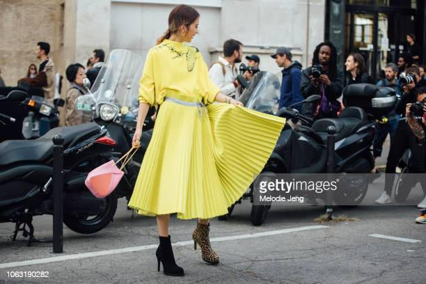 Irene Kim wears a yellow Sacai sweater and pleated skirt at the Sacai show and mixmatch booties during Paris Fashion Week Spring/Summer 2019 on...