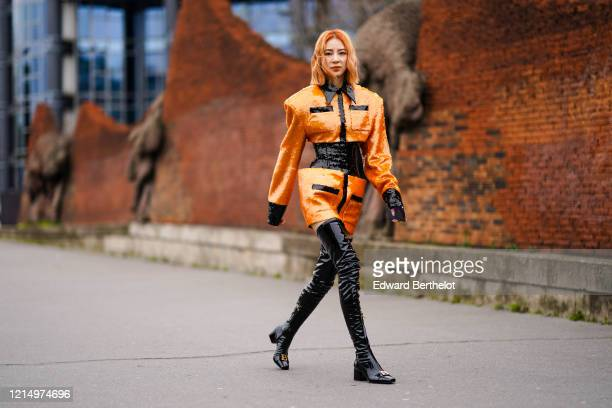 Irene Kim wears an orange and black glittering shiny oversized jacket/dress with long sleeves, pockets and integrated corset, black shiny pvc thigh...