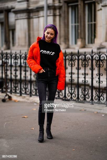 Irene Kim wears an orange puffer jacket a black top 'Paris' black pants outside Thom Browne during Paris Fashion Week Womenswear Spring/Summer 2018...