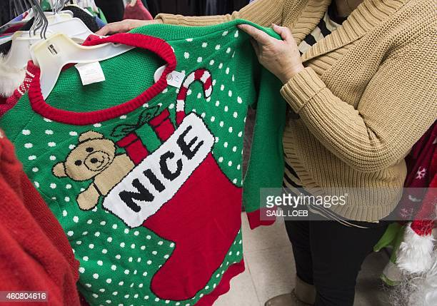 Irene Lopez manager of Frugalista second hand store shows off the store's supply of 'ugly' Christmas sweaters in Washington DC December 23 2014...
