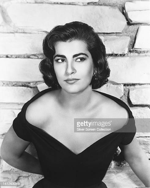 Irene Papas Greek actress wearing a black offtheshoulder dress posing against a whitepainted brick wall circa 1955