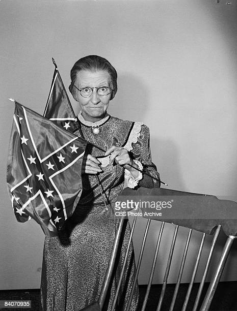 Irene Ryan holds up a pair of Confederate flags as Daisy Moses the grandmother character in the television comedy 'The Beverly Hillbillies' 1965 This...