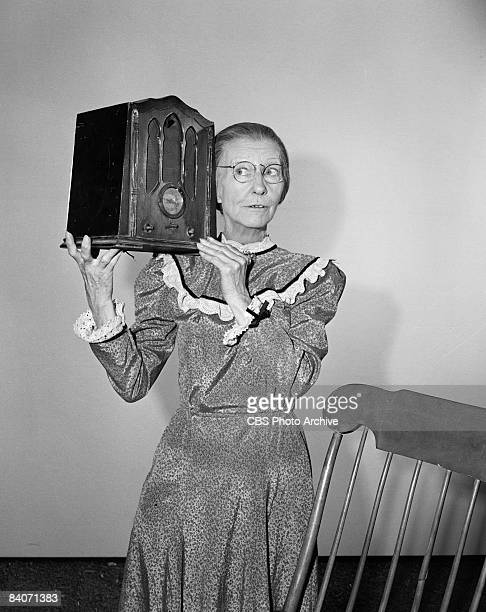 Irene Ryan listens to an oldfashioned radio she has hoisted onto her shoulder as Daisy Moses the grandmother character in the television comedy 'The...