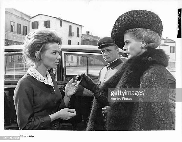 Irina Demick is given a piece of jewelry from Ingrid Bergman in a scene from the film 'The Visit', 1964.