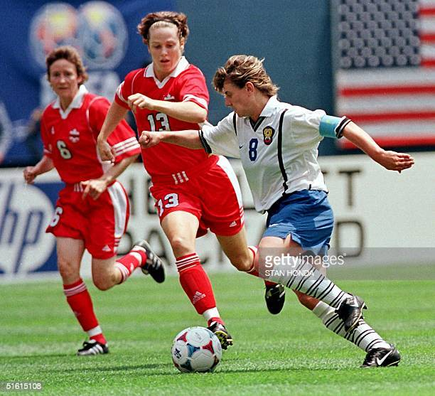 Irina Grigorieva of Russia pushes the ball past Canadians Amy Walsh and Geri Donnelly in the first half in the first round of Women's World Cup 26...
