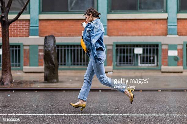 Irina Lakicevic wearing a denim jacket and denim jeans and yellow heels and clutch seen outside Rodarte during New York Fashion Week Women's...