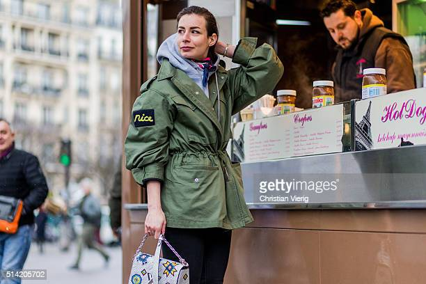 Irina Lakicevic wearing a green parka and silver Louis Vuitton bag in front of a crepes kiosk outside Sacai during the Paris Fashion Week Womenswear...