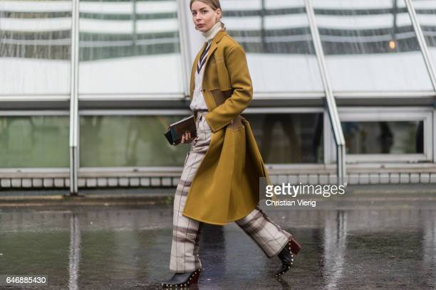 Irina Lakicevic wearing a mustard coat checked pants outside Dries Van Noten on March 1 2017 in Paris France