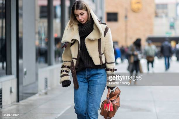 Irina Lakicevic wearing a turtleneck knit beige sheepskin jacket Loewe bag denim outside Creatures of the Wind on February 11 2017 in New York City