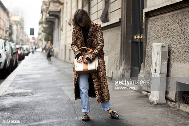 Irina Lakicevic wears leopard print trench coat Gucci Princetown leather slipper fur loafers and buttons her cream/tan tote bag at the Antonio Marras...