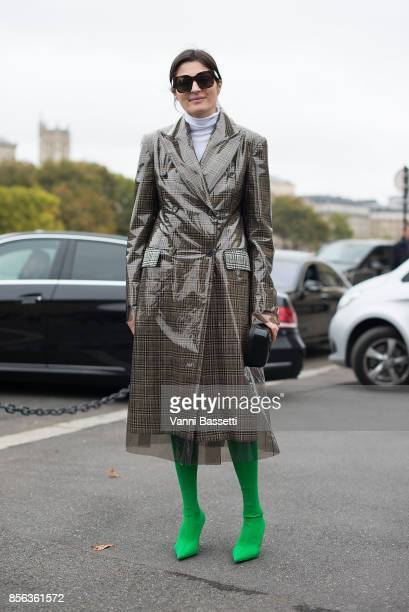 Irina Linovich poses wearing a Calvin Klein trenchcoat and Balenciaga boots after the Givenchy show at the Palais de Justice during Paris Fashion...