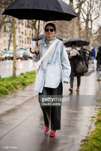 Irina Linovich wearing a long light blue denim shirt black leather pants red snake print boots and white bag is seen outside Loewe on Day 5 Paris...