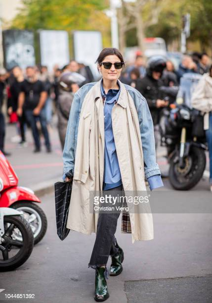 Irina Linovich wearing trench coat worn as scarf denim jacket cropped denim jeans ankle boots is seen outside Sacai during Paris Fashion Week...