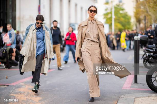 Irina Linovich wearing trench coat worn as scarf denim jacket cropped denim jeans ankle boots and Julie Pelipas wearing beige trench coat pants...