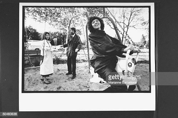 Irina Ratushinskaya Russian emigre poet human rights activist sitting on a playground swing w husband Igor Gerashchenko old friend Larisa Meyerovich...