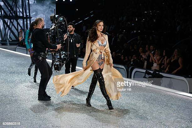 Irina Shayk walks the runway as The Weeknd performs during the 2016 Victoria's Secret Fashion Show at Le Grand Palais on November 30 2016 in Paris...